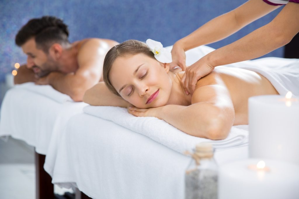 Couple Getting Massage Together in Spa Center